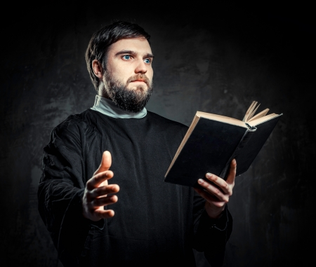 predicador: Sacerdote con libro de Oración contra el fondo oscuro Foto de archivo