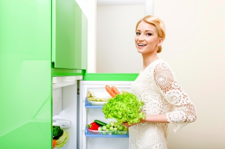 Smiling young woman taking vegetables out of fridge Stock Photo - 17398827
