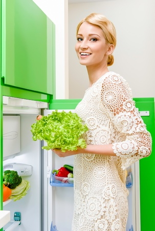 Smiling young woman taking vegetables out of fridge photo