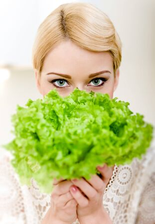 Portrait of beautiful blond woman hiding behind lettuce photo