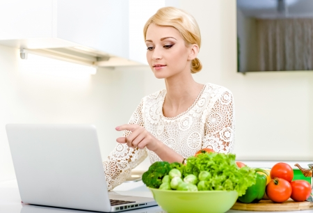 Young woman looking for a recipe on the laptop computer in the kitchen  Dieting Concept  Vegetarian food Stock Photo - 17398724