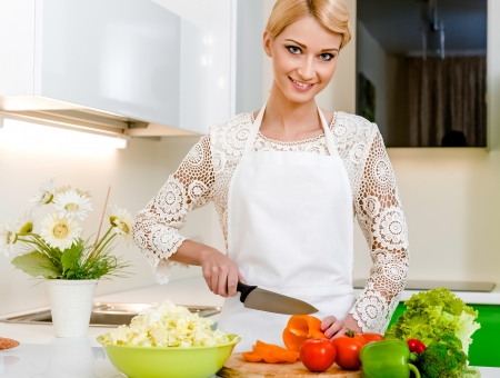 Smiling young woman preparing vegetarian salad Stock Photo - 17399436