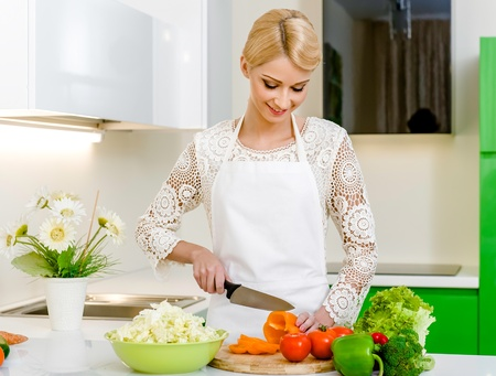 Smiling young woman preparing vegetarian salad Stock Photo - 17399407