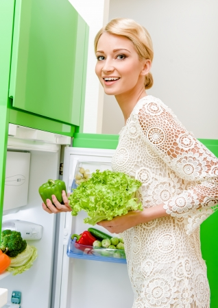 refrigerator with food: Smiling young woman taking vegetables out of fridge