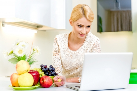 Young woman looking for a recipe on the laptop computer in the kitchen. Dieting Concept.  Stock Photo - 17482861