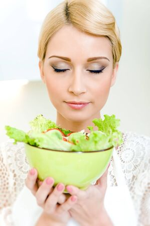 Portrait of a beautiful young woman holding a bowl with vegetable salad Stock Photo - 17482856