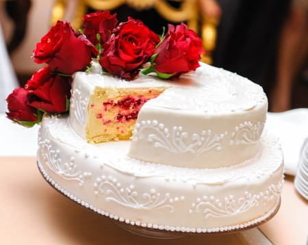 Wedding cake decorated with red roses photo