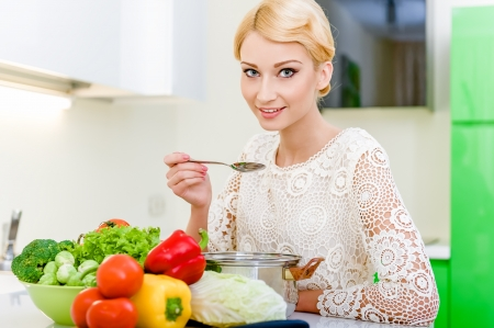 beautiful salad: Young woman tasting soup.Healthy Vegetarian Food. Dieting Concept. Healthy Lifestyle. Cooking At Home. Stock Photo