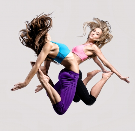 Two beautiful athletic girl jumping  photo