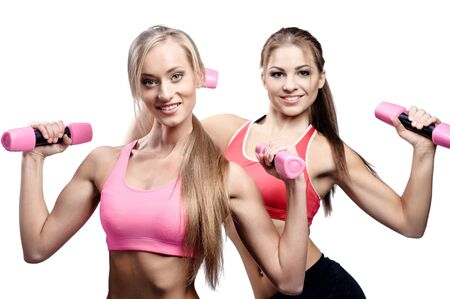 sporting activity: Two beautiful young woman doing fitness exercise with dumbbells Stock Photo