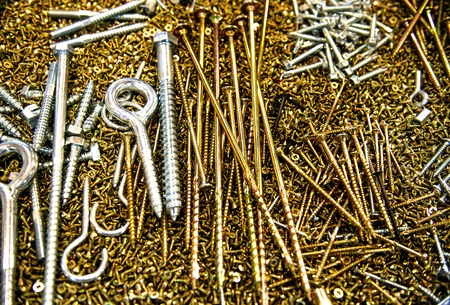 screw heads: Pile of gold and silver screws, various shapes and sizes for different purposes
