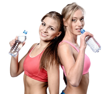 Two beautiful young women drinking water after fitness exercise Stock Photo - 18817122