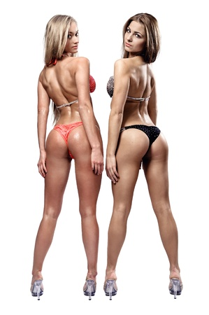 Two beautiful athletic girl wearing bikini posing over white background photo