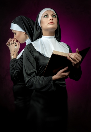 convent: Two attractive young nuns with rosary beads and bible