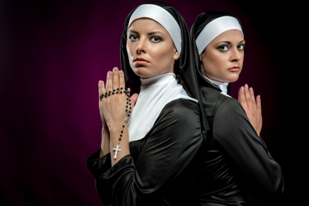 Portrait of two attractive young nuns praying photo
