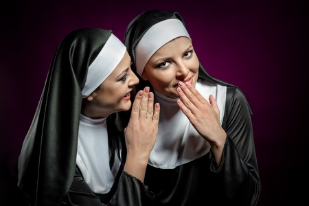 priesthood: Young attractive nun whispering a secret to another nun  Stock Photo