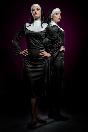 Two attractive young nuns posing indoors photo