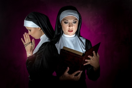 convent: Two attractive young nuns with rosary and bible praying