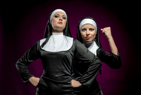 convent: Two attractive young nuns posing indoors Stock Photo