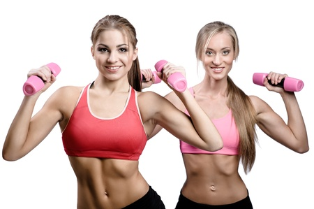 Two beautiful young women doing fitness exercise with dumbbells photo