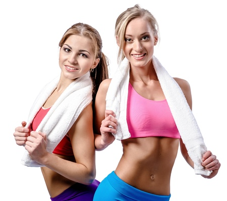 Two beautiful girls after workout with towels isolated on white background photo