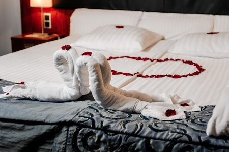 just married: Honeymoon bed decorated with red rose petals and towels