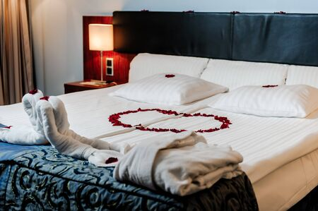 heart suite: Honeymoon bed decorated with red rose petals and towels
