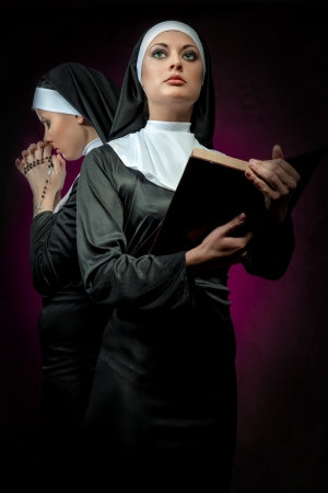 Two attractive young nuns with rosary and bible praying photo
