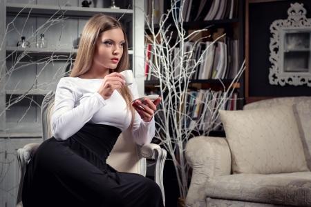 donna ricca: Giovane e bella donna che beve il caff� in interni di lusso d'epoca