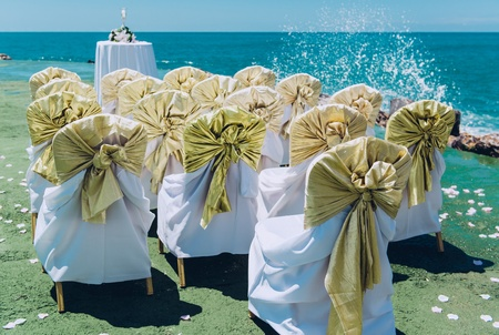 Row of wedding white chairs decorated with golden bows on the beach photo