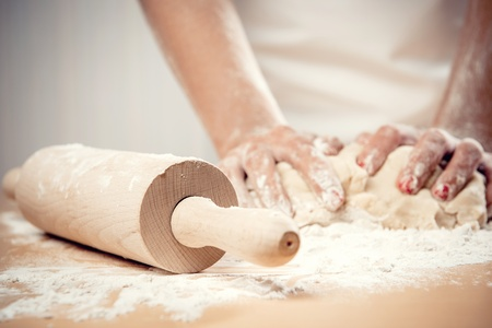 knead: Woman kneading dough, close-up photo