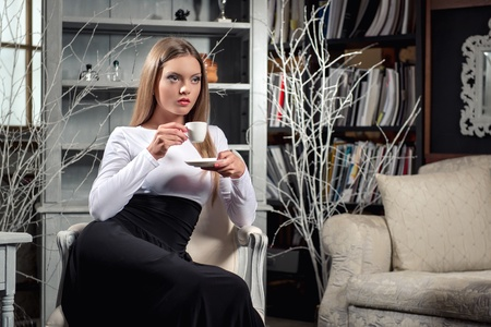 styled interior: Young beautiful woman drinking coffee in luxury vintage interior