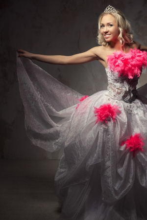 feather boa: Lovely woman wearing white dress decorated with pink feather boa posing indoors Stock Photo