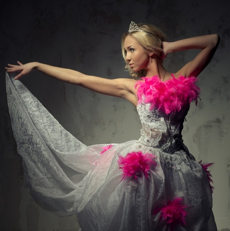 Lovely woman wearing white dress decorated with pink feather boa posing indoors photo