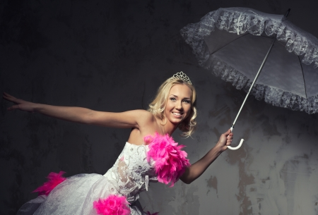 Beautiful bride with lace umbrella posing indoors photo