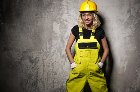 studio happy overall: Attractive builder woman posing against grunge wall