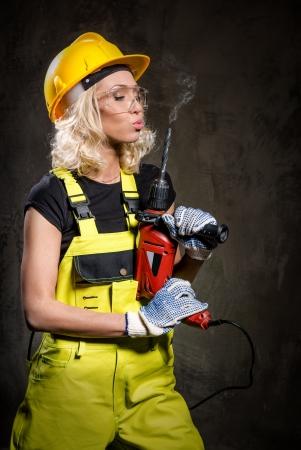 Aantrekkelijke builder vrouw met een boor in haar handen