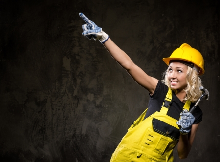 studio happy overall: Attractive builder woman showing something with the hand, studio shot