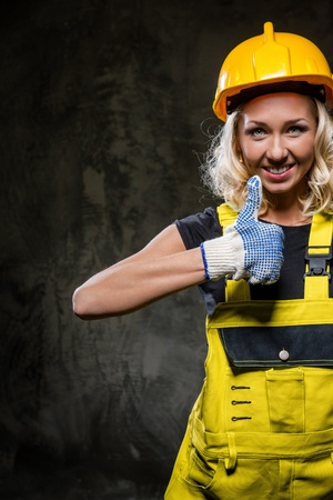 studio happy overall: Attractive builder woman with thumbs up  Stock Photo