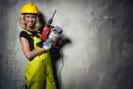 Attractive builder woman with a drill in her hands photo