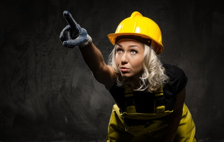 Attractive builder woman showing something with the hand, studio shot photo