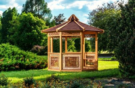 夏の風景の背景の上の屋外の木製ガゼボ 写真素材