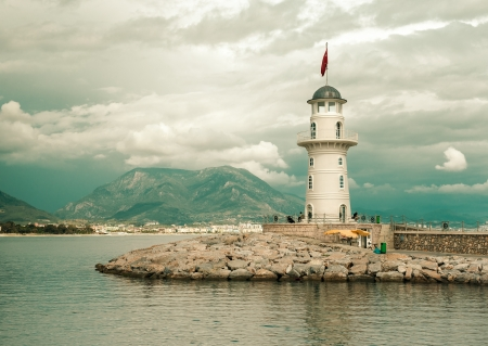 lighthouses: Beautiful nature landscape with mountains range, cloudy sky and lighthouse in port Alanya, Turkey