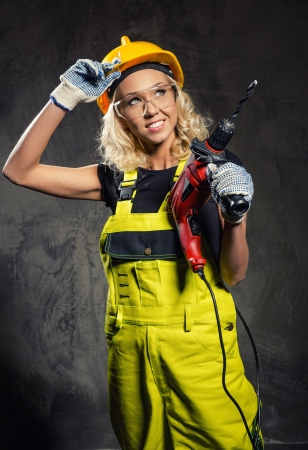 Attractive builder woman with a drill in her hands Stock Photo - 20386112