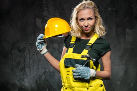 Attractive builder woman with protective helmet posing against grunge wall photo