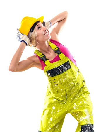 studio happy overall: Female construction worker in coverall and hardhat posing over obsolete background Stock Photo