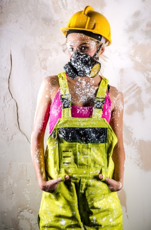 dust mask: Female construction worker wearing coverall, hardhat and respirator posing over obsolete wall