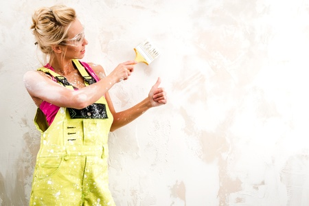 Female worker in coverall paint a  wall and showing thumbs up Stock Photo