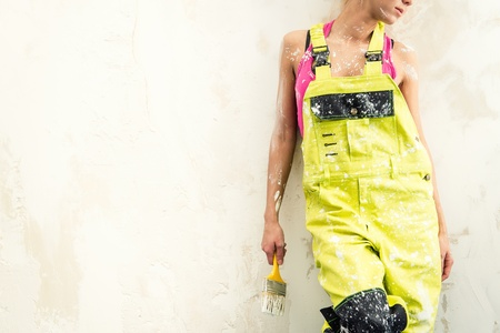coverall: Female in coverall holding paint brush over obsolete white background