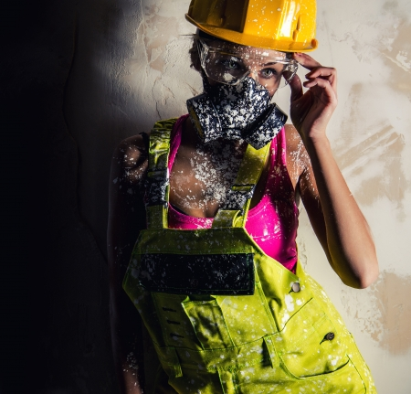 respirator: Female construction worker wearing coverall, hardhat and respirator posing over obsolete wall